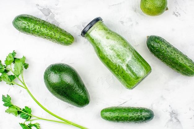 На светлом фоне бутылка с смузи из огурца, авокадо и петрушки.