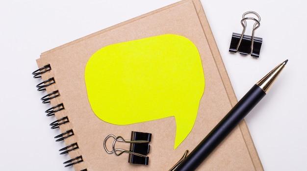 На светлом фоне коричневый блокнот, черная ручка и скрепки, а также желтая карточка с местом для вставки текста. бизнес-концепция. шаблон