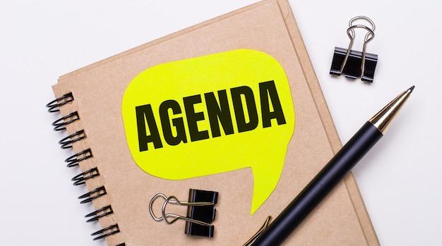 明るい背景に、茶色のノート、黒いペンとペーパークリップ、およびテキストagendaの付いた黄色のカード。ビジネスコンセプト。