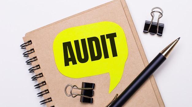 На светлом фоне коричневая тетрадь, черная ручка и скрепки, а также желтая карточка с текстом audit. бизнес-концепция.