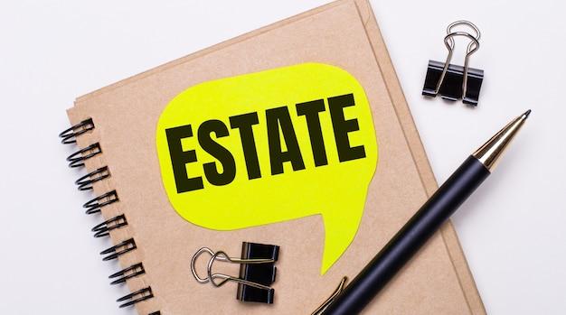 На светлом фоне коричневый блокнот, черная ручка и скрепки, а также желтая карточка с надписью estate. бизнес-концепция.