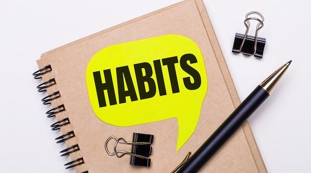 明るい背景に、茶色のノート、黒いペンとペーパークリップ、および「習慣」というテキストが記載された黄色のカード。ビジネスコンセプト。