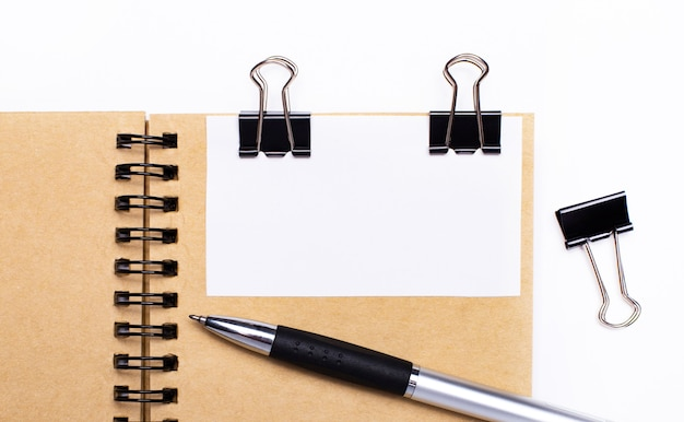 На светлом фоне коричневая тетрадь с ручкой, черными зажимами и белой карточкой с местом для вставки текста или иллюстраций. шаблон.