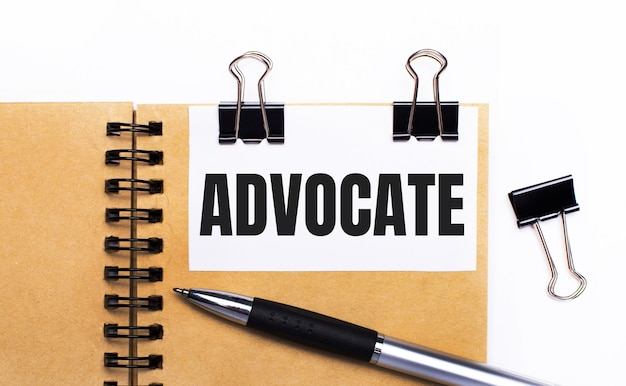 На светлом фоне коричневый блокнот с ручкой, черными зажимами и белой карточкой с текстом advocate.