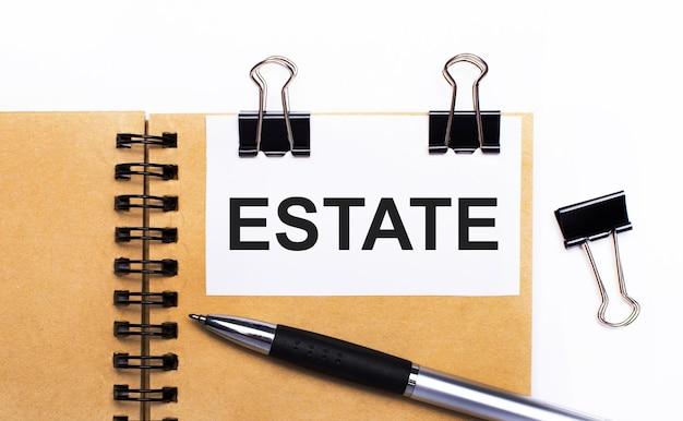 На светлом фоне коричневый блокнот с ручкой, черными зажимами и белой карточкой с текстом estate.