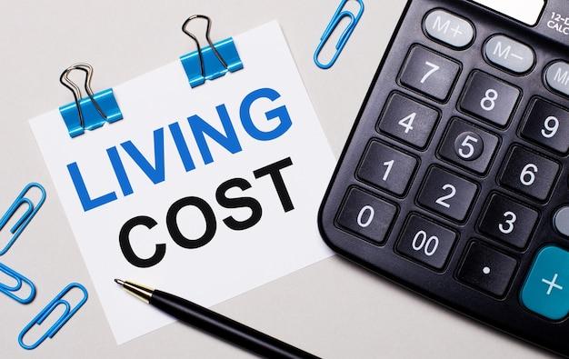 На светлом фоне калькулятор, ручка, синие скрепки и лист бумаги с текстом стоимость жизни. вид сверху