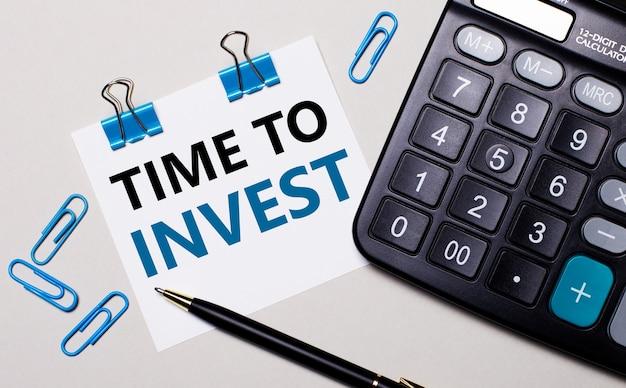 밝은 배경에 계산기, 펜, 파란색 종이 클립 및 time to invest라는 텍스트가있는 종이. 위에서보기