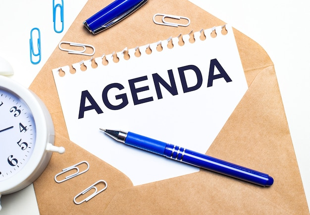明るい背景に、クラフト封筒、目覚まし時計、ペーパークリップ、青いペン、agendaというテキストが書かれた紙。