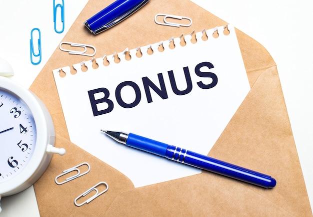 На светлом фоне крафт-конверт, будильник, скрепки, синяя ручка и лист бумаги с текстом бонус.