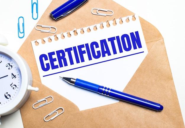 На светлом фоне крафт-конверт, будильник, скрепки, синяя ручка и лист бумаги с текстом сертификация.
