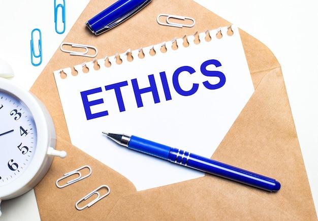 明るい背景に、クラフト封筒、目覚まし時計、ペーパークリップ、青いペン、ethicsというテキストが書かれた紙。