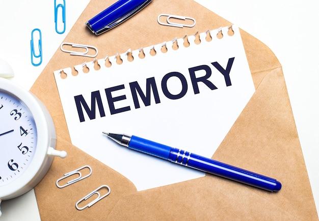 明るい背景に、クラフト封筒、目覚まし時計、ペーパークリップ、青いペン、memoryというテキストが書かれた紙。