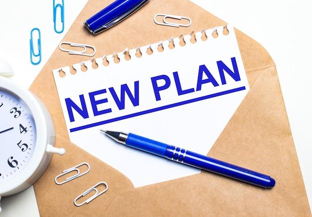 На светлом фоне крафт-конверт, будильник, скрепки, синяя ручка и лист бумаги с текстом new plan.