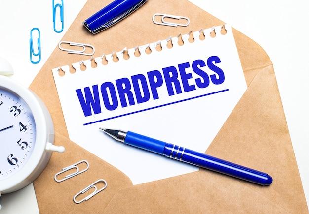 На светлом фоне крафт-конверт, будильник, скрепки, синяя ручка и лист бумаги с надписью wordpress.