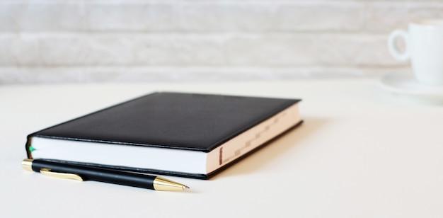 明るい背景に、濃い青のノートとペン。閉じる