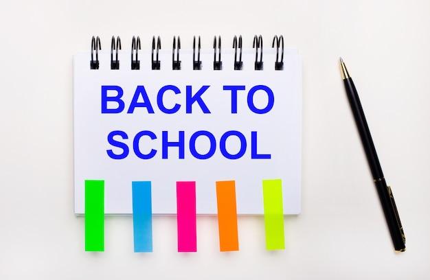 밝은 배경에 펜, back to school이라는 텍스트가 있는 노트북 및 밝은 스티커.