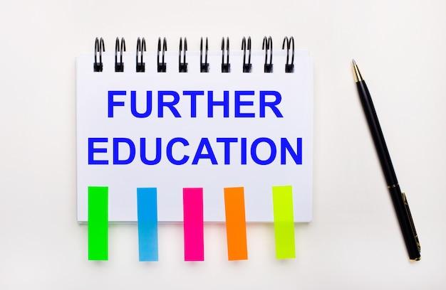 明るい背景に、ペン、「further education」というテキストが書かれたノート、明るいステッカー。