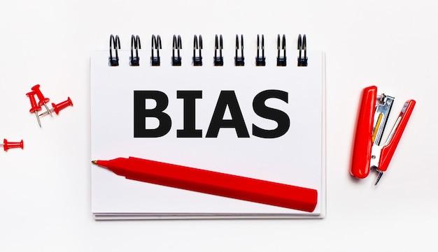 На светлом фоне красная ручка, красный степлер, красные скрепки и блокнот с надписью bias.