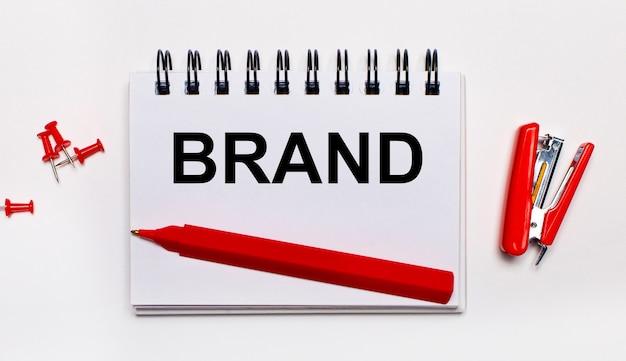 На светлом фоне красная ручка, красный степлер, красные скрепки и блокнот с надписью brand.