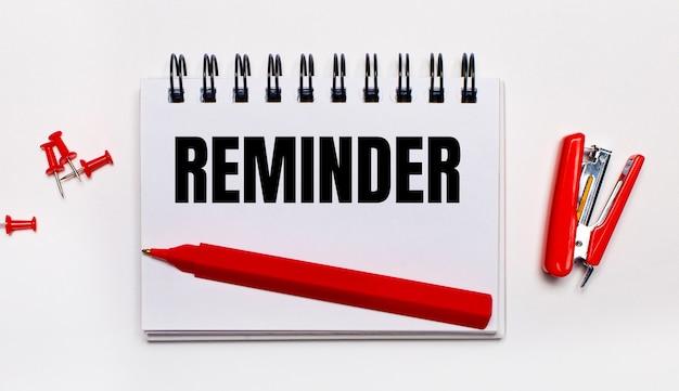 明るい背景に、赤いペン、赤いホッチキス、赤いペーパークリップ、reminderの碑文が書かれたノート