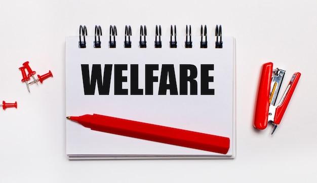 На светлом фоне красная ручка, красный степлер, красные скрепки и блокнот с надписью welfare.