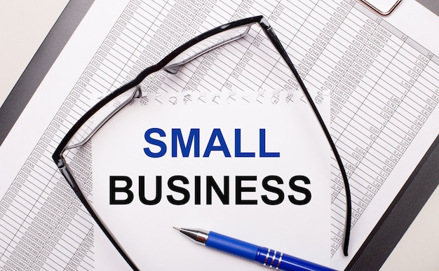 明るい背景に、レポート、黒いフレームのメガネ、ペン、そして「smallbusiness」というテキストが書かれた1枚の紙。ビジネスコンセプト