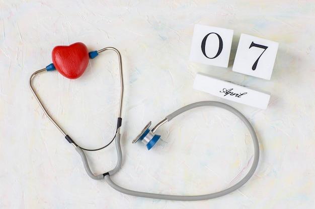 На светлом фоне стейкоскоп и красное сердце и календарная дата 7 апреля