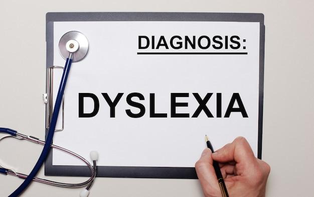 明るい背景に、聴診器と一枚の紙に、男性がディスレクシアを書いています。医療コンセプト