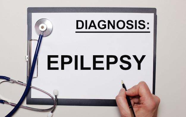На светлом фоне стетоскоп и лист бумаги, на котором мужчина пишет эпилепсия. медицинская концепция
