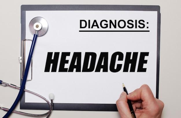 На светлом фоне стетоскоп и лист бумаги, на котором мужчина пишет «головная боль». медицинская концепция