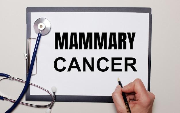 明るい背景に、聴診器と1枚の紙に、男性がmammarycancerと書いています。医療の概念