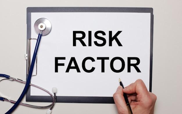 На светлом фоне стетоскоп и лист бумаги, на котором мужчина пишет фактор риска.