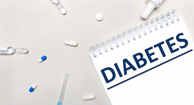 На светлом фоне шприц, стетоскоп, пузырьки с лекарством, ампула и белый блокнот с надписью diabetes. медицинская концепция