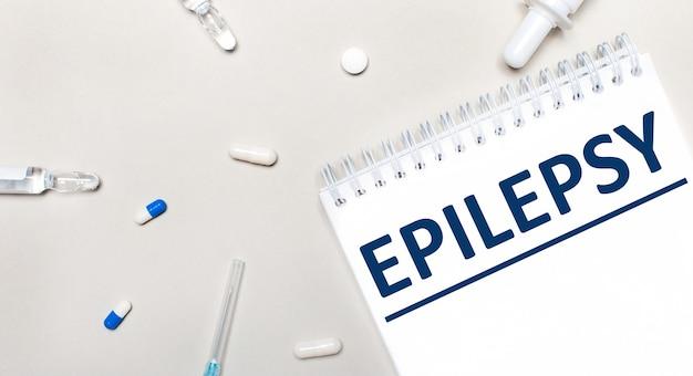 На светлом фоне шприц, стетоскоп, пузырьки с лекарством, ампула и белый блокнот с надписью эпилепсия. медицинская концепция