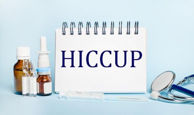 明るい背景に、注射器、聴診器、薬瓶、アンプル、hiccupというテキストの白いメモ帳