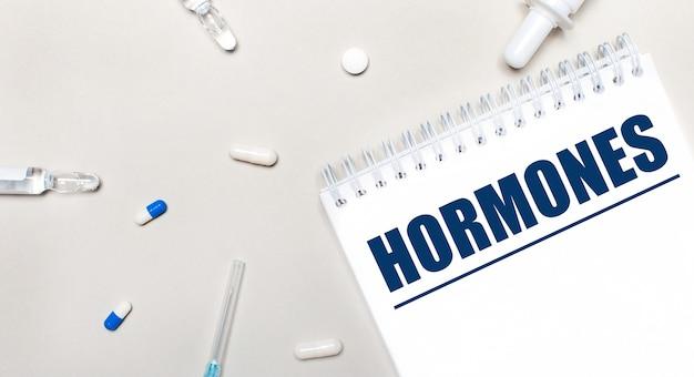 На светлом фоне шприц, стетоскоп, пузырьки с лекарством, ампула и белый блокнот с текстом hormones. медицинская концепция