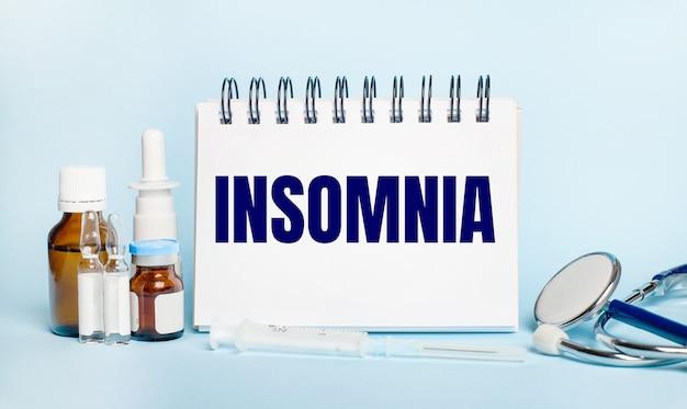 На светлом фоне шприц, стетоскоп, пузырьки с лекарством, ампула и белый блокнот с надписью insomnia. медицинская концепция