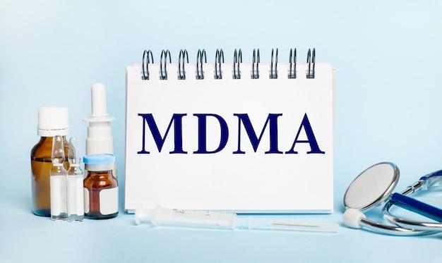 На светлом фоне шприц, стетоскоп, пузырьки с лекарством, ампула и белый блокнот с текстом mdma. медицинская концепция