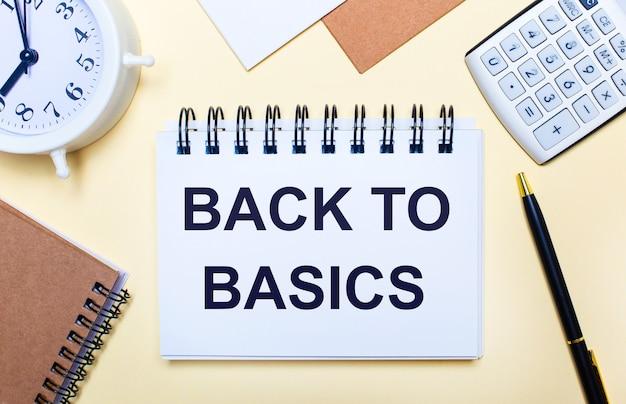 明るい背景に、白い目覚まし時計、電卓、ペン、「基本に戻る」というテキストのノート