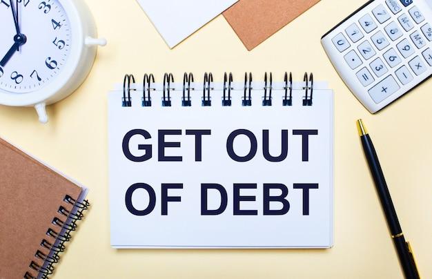 明るい背景に、白い目覚まし時計、電卓、ペン、「get outofdebt」というテキストが書かれたノート。フラットレイ