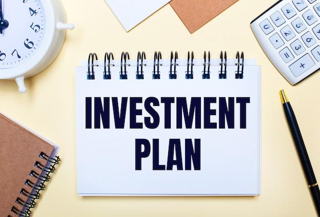 На светлом фоне белый будильник, калькулятор, ручка и блокнот с текстом инвестиционный план. плоская планировка
