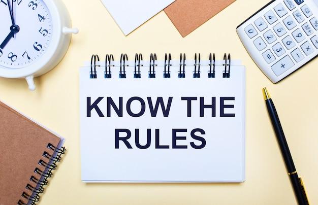 明るい背景に、白い目覚まし時計、電卓、ペン、「ルールを知っている」というテキストのノート