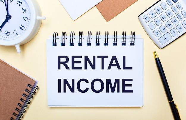 На светлом фоне белый будильник, калькулятор, ручка и блокнот с текстом аренда дохода. плоская планировка