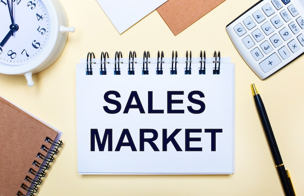 На светлом фоне белый будильник, калькулятор, ручка и блокнот с текстом «рынок продаж». плоская планировка