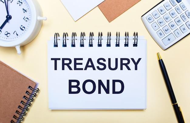 На светлом фоне белый будильник, калькулятор, ручка и блокнот с текстом treasury bond.