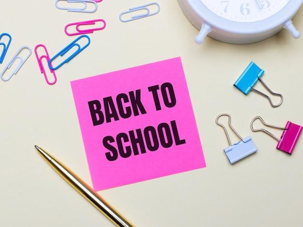 明るい背景に、白い目覚まし時計、ピンク、青、白のペーパークリップ、金色のペン、ピンクのステッカーとテキストback to school