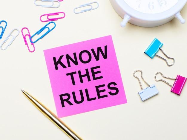 На светлом фоне белый будильник, розовые, синие и белые скрепки, золотая ручка и розовая наклейка с текстом know the rules.