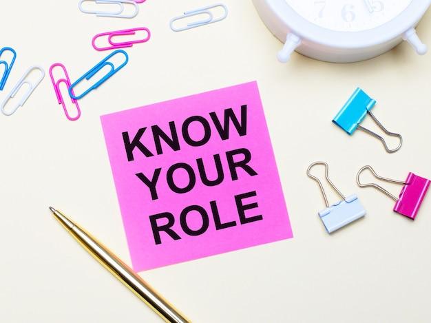 На светлом фоне белый будильник, розовые, синие и белые скрепки, золотая ручка и розовая наклейка с надписью know your role.