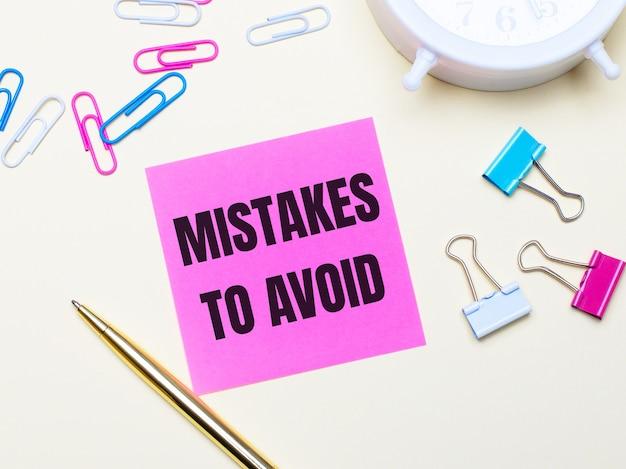 明るい背景に、白い目覚まし時計、ピンク、青、白のペーパークリップ、金色のペン、ピンクのステッカーに「間違いを避ける」というテキストが付いています