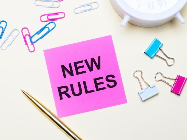 На светлом фоне белый будильник, розовые, синие и белые скрепки, золотая ручка и розовая наклейка с текстом новые правила.